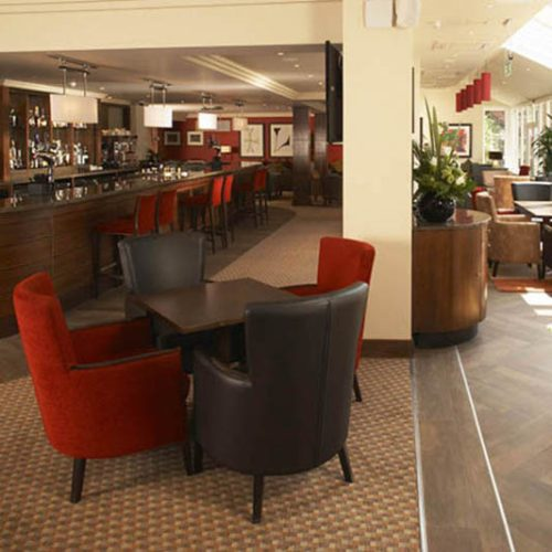 Hotel bar and dining area with red and brown armchairs