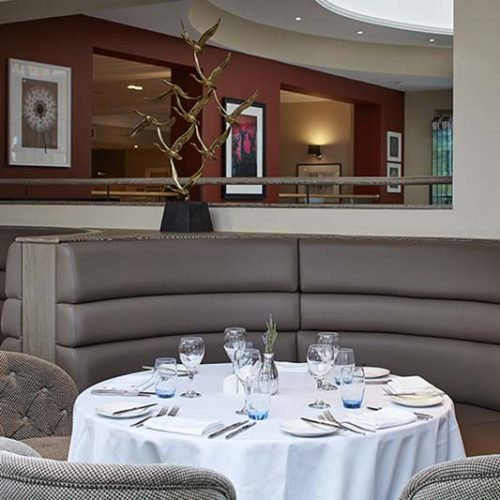 Hotel dining area with grey banquette seating