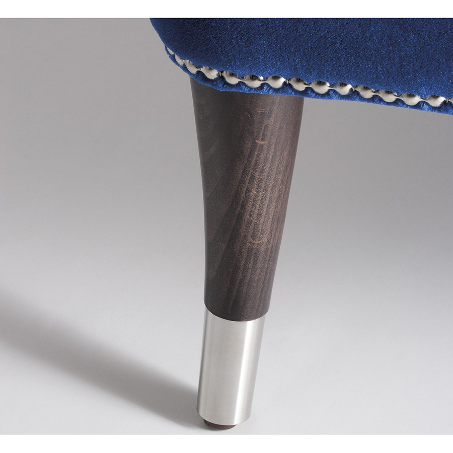 Close-up of wooden chair leg with chrome cap